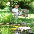 Kerti tó mellett elhelyezett larin növényfuttató keret a háttérben egy padon ülő hölggyel